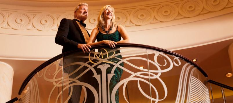 Couple in formal wear on the Grand Lobby staircase | The Cunard Experience
