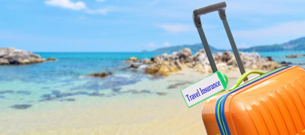 Suitcase on beach | The cost of not having travel insurance
