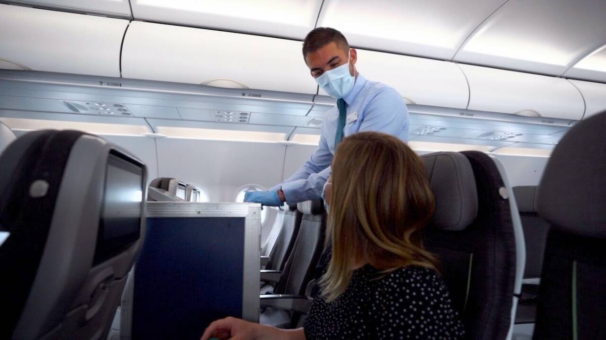 Aer Lingus cabin crew wearing a mask and gloves interacting with a passenger